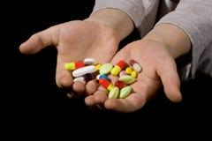 Pilules colorées sur des mains Photo stock