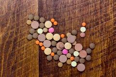 Pilules colorées sur le fond en bois photo stock