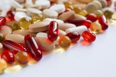 Pilules colorées sur une surface blanche Photographie stock libre de droits