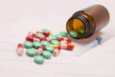 Pilules colorées, une bouteille et une seringue Photographie stock