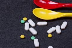 Pilules, comprimés et capsules pharmaceutiques assortis de médecine sur la cuillère Images libres de droits