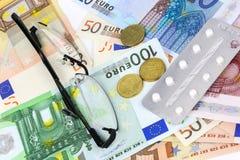 Pilules, comprimés et verres médicaux dans d'euro billets de banque Photos stock