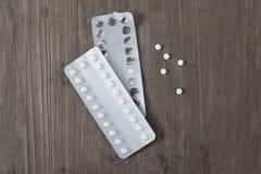 pilules contraceptives sur une table en bois photos stock