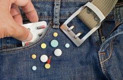Pilules dans la poche de jeans Image libre de droits