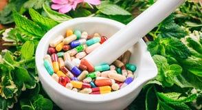 Pilules dans un mortier sur un fond frais d'herbes images libres de droits