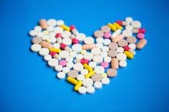Pilules dans un plan rapproché de forme de coeur photographie stock libre de droits