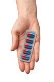 Pilules dans une main d'isolement sur le fond blanc médecine Photo libre de droits