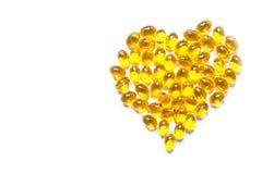 Pilules de capsule d'huile de poisson de couleur jaune sous forme de plan rapproché de coeur d'isolement Photo libre de droits