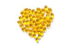 Pilules de capsule d'huile de poisson de couleur jaune sous forme de plan rapproché de coeur d'isolement Photos stock