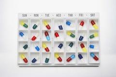 Pilules de capsule dans le récipient avec des jours Images libres de droits
