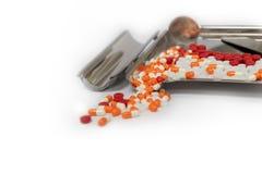 Pilules de capsules et plateau oranges de drogue sur le fond blanc avec la cannette de fil photographie stock libre de droits