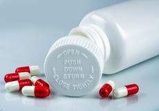 Pilules de capsules sur la bouteille blanche de fond et de plastique avec l'espace vide de label et de copie Emballage sans dange Photographie stock libre de droits