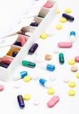 Pilules de couleur et capsules dans et hors d'organisateur de pilule Photographie stock