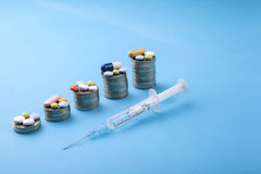 Pilules de médecine et capsules et pièces de monnaie sur un fond bleu Image stock