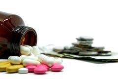 Pilules de médecine, vitamines et bouteille sur la pièce de monnaie brouillée d'argent et fond blanc avec l'espace de copie photo stock