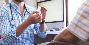Pilules de prescription de docteur masculin ? son patient masculin sup?rieur dans la clinique images libres de droits