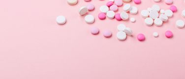Pilules de rose et blanches sur le fond rose Tas de divers comprimés et pilules assortis de médecine Banni?re horizontale photographie stock libre de droits
