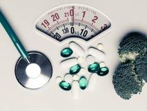 Pilules de stéthoscope de brocoli sur l'échelle de poids dieting Image stock