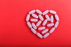 Pilules dispersées comme coeur Photographie stock libre de droits