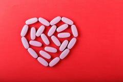 Pilules dispersées comme coeur Photographie stock