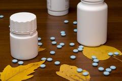 Pilules et bouteille bleues de médecine sur en bois Image stock