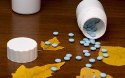 Pilules et bouteille bleues de médecine sur en bois Images stock
