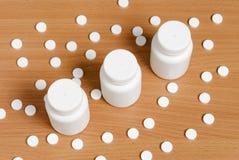 Pilules et bouteilles sur la surface en bois Photographie stock libre de droits