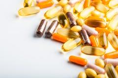 Pilules et capsules d'isolement multicolores image stock