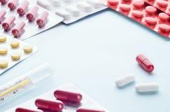 Pilules et capsules dans une boursouflure et un thermomètre Image libre de droits