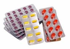 Pilules et capsules de médecine emballées dans des ampoules Image stock