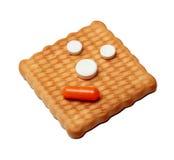 Pilules et capsules médicales sur un biscuit d'isolement sur le backgro blanc Images stock