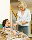 Pilules et eau de offre de femme agée au retraité Photographie stock