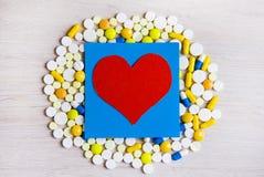 Pilules et forme de coeur photographie stock