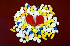 Pilules et forme de coeur photos stock