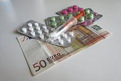 Pilules et injection sur l'euro billet de banque - assurance Images libres de droits