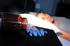 Pilules et jeune homme dans le lit Image libre de droits