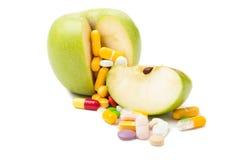 Pilules et pomme Photographie stock