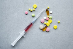 Pilules et seringue dispersées Photographie stock