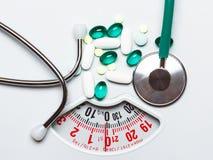 Pilules et stéthoscope sur des échelles Soins de santé Photographie stock libre de droits