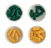 Pilules et Tablettes pharmaceutiques de médecine dans des tasses en plastique blanches d'isolement Photos stock