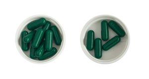 Pilules et Tablettes pharmaceutiques de médecine dans des tasses en plastique blanches d'isolement Images stock