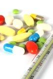 Pilules et termometr médicaux multicolores Photographie stock libre de droits