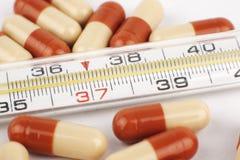 Pilules et thermomètre Photographie stock libre de droits