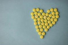 Pilules jaunes de petit rond pharmaceptic médical, vitamines, drogues, antibiotiques sous forme de coeur sur un fond bleu, textur photographie stock libre de droits