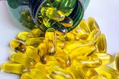 Pilules jaunes en dehors de sa bouteille verte Photographie stock libre de droits