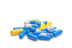 Pilules jaunes et bleues de médecine sur le fond blanc d'isolement Photographie stock libre de droits