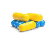 Pilules jaunes et bleues de médecine sur le fond blanc d'isolement Images libres de droits
