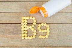 Pilules jaunes formant la forme à l'alphabet B9 sur le fond en bois Image stock