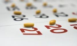 Pilules jaunes sur un calendrier photographie stock libre de droits