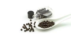 Pilules noires de médecine traditionnelle ou de bol noir près de bouteille photos libres de droits
